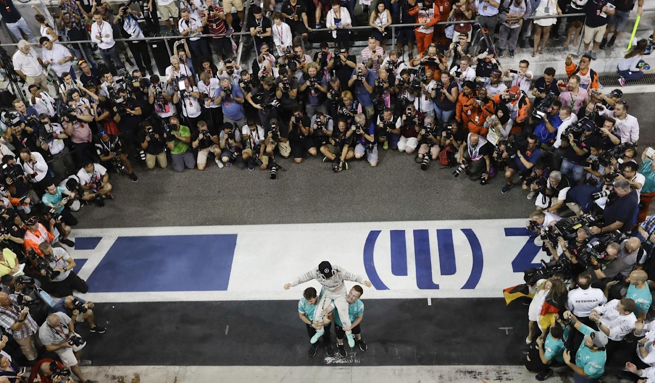 In this picture taken on Sunday, Nov. 27, 2016, Mercedes driver Nico Rosberg of Germany celebrates in the team garage after winning the F1 2016 Championship in the Emirates Formula One Grand Prix at the Yas Marina racetrack in Abu Dhabi, United Arab Emirates. Rosberg's announcement on Friday, Dec. 2, 2016 that he was retiring at the age of 31, five days after earning his first Formula One world championship, shocked the world of motor racing. (AP Photo/Luca Bruno)