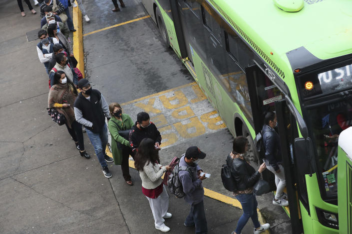 Commuters, most who use the Line 12 subway daily to get across the city, line up to board buses on the south side of Mexico City, Thursday, May 6, 2021, after a Monday collapse on Line 12 left it out of service. At its farthest point, Line 12 carries commuters from the capital's still semi-rural south side to jobs across the city. Some 220,000 riders use Line 12 every day. (AP Photo/Marco Ugarte)