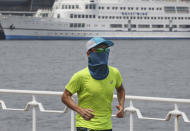 A man wearing a face mask to protect against the spread of the new coronavirus runs at along the waterfront in Yokohama near Tokyo, Monday, Aug, 10, 2020. (AP Photo/Koji Sasahara)