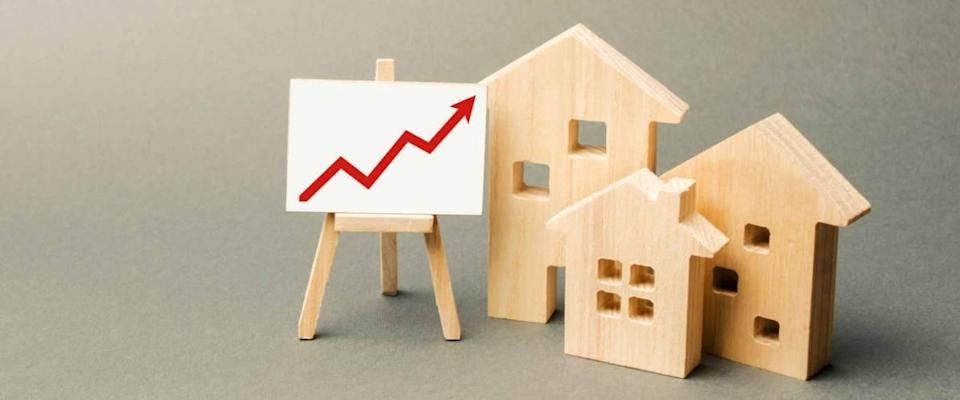 three wooden houses and a red upward arrow on the sign. Increase in real estate value. High construction rates, high liquidity. Supply and demand. Higher housing prices, building maintenance.