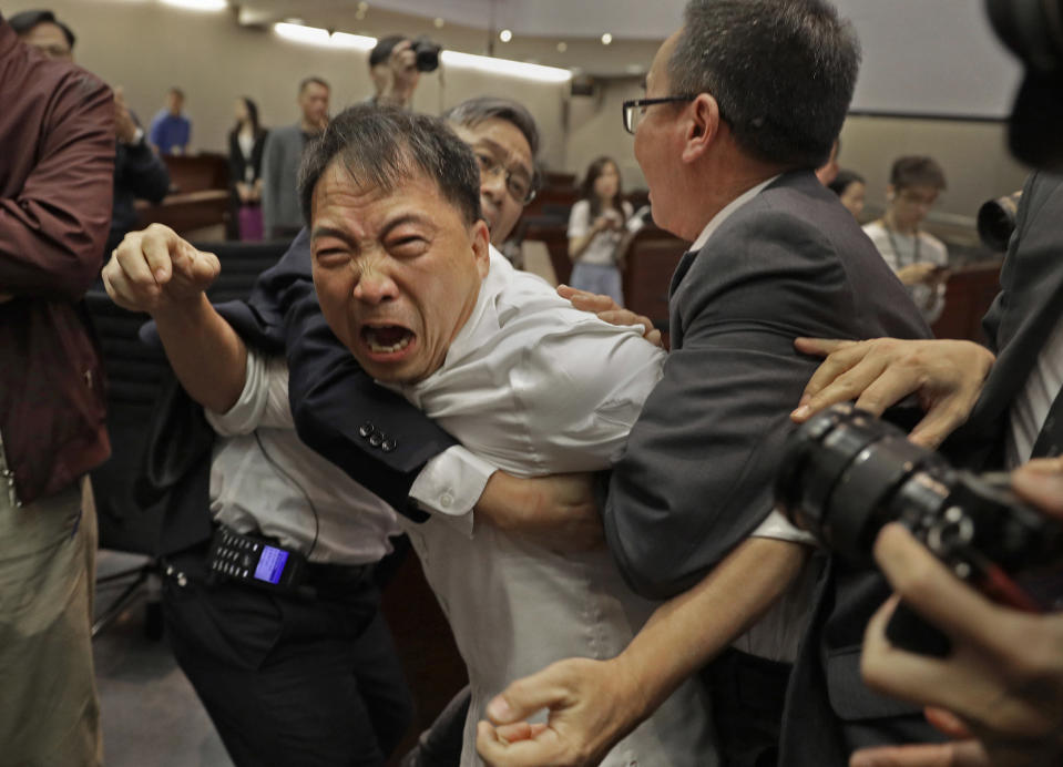 FILE - In this May 11, 2019, file photo, pro-democracy lawmaker Wu Chi-wai, center, scuffles with security guards at Legislative Council in Hong Kong. After nearly three decades in politics, the 58-year-old Wu, chairman of Hong Kong's largest pro-democracy party, is stepping down Monday, Nov. 30, 2020. All 15 lawmakers in the pro-democracy camp have decided to resign to protest a Beijing resolution in early November that led to the disqualifications of four of their colleagues. (AP Photo/Vincent Yu, File)