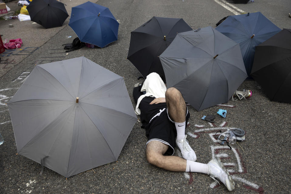 A pro-democracy protester takes a rest near umbrellas placed on a road outside the Chinese University campus in Hong Kong, Wednesday, Nov. 13, 2019. Police increased security around Hong Kong and its university campuses as they brace for more violence after sharp clashes overnight with anti-government protesters. (AP Photo/Ng Han Guan)