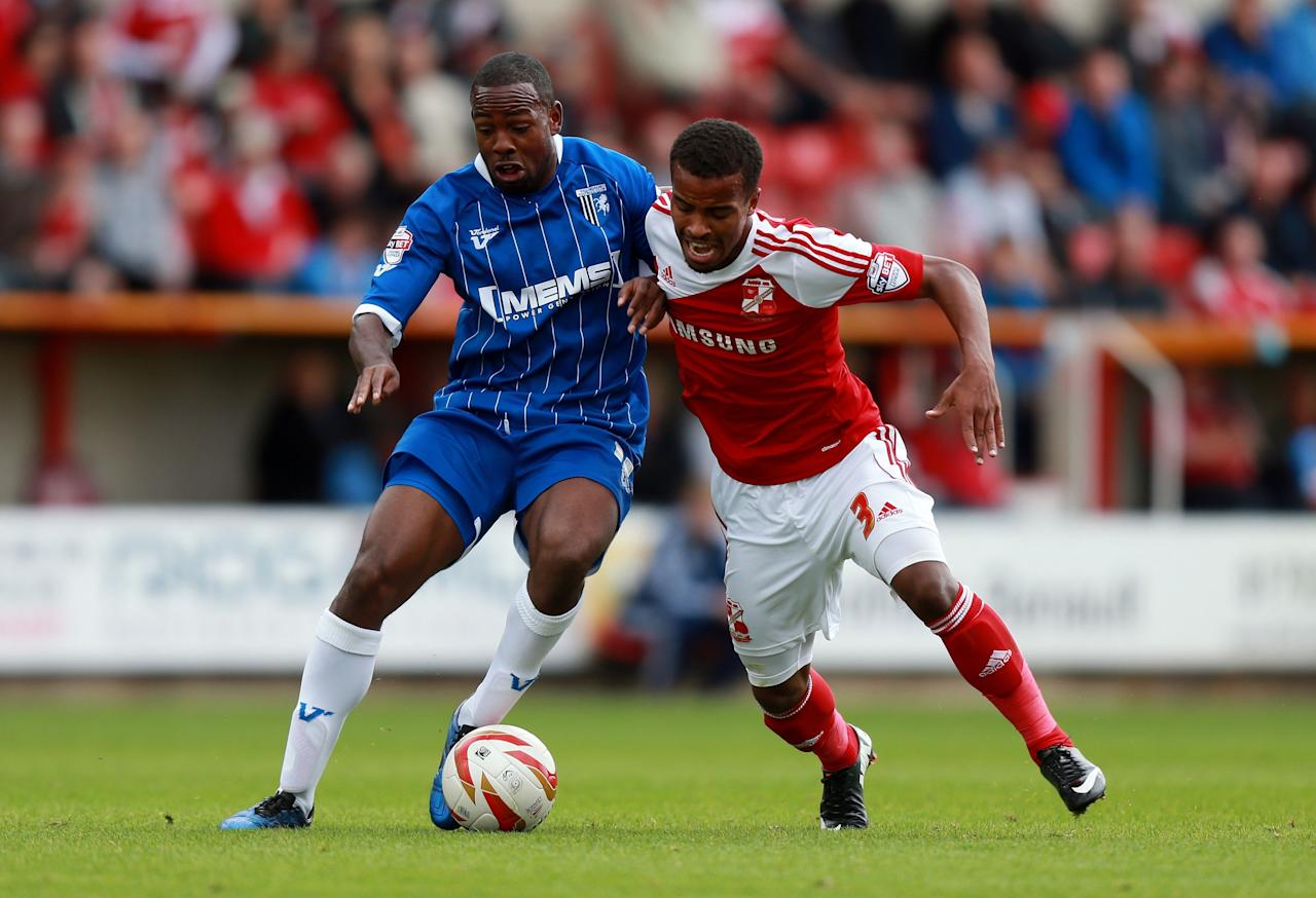 Gillingham's Myles Weston is challenged by Swindon's Nathan Byrne during the Sky Bet Football League One match at the County Ground, Swindon.