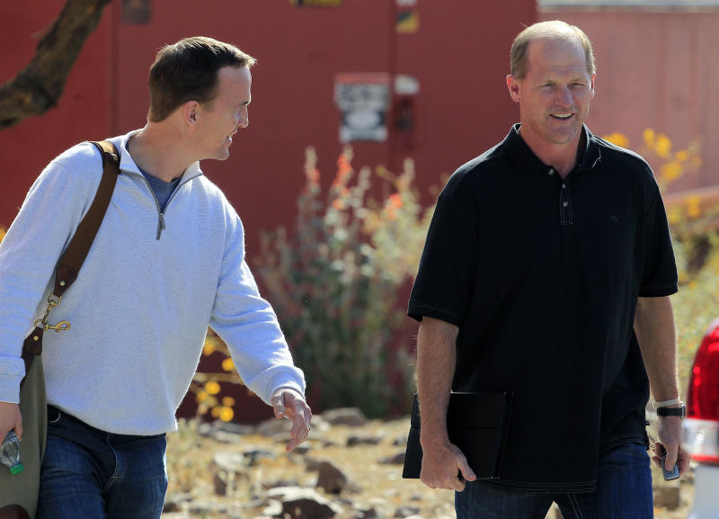 NFL quarterback Peyton Manning, left, leaves the Arizona Cardinals training facility after a five hour meeting with coaches, including head coach Ken Whisenhunt, right, and front office staff Sunday, March 11, 2012, in Tempe, Ariz.(AP Photo/Ross D. Franklin)