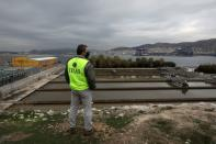 An employee gathers sewage samples at a wastewater treatment plant on the island of Psyttalia