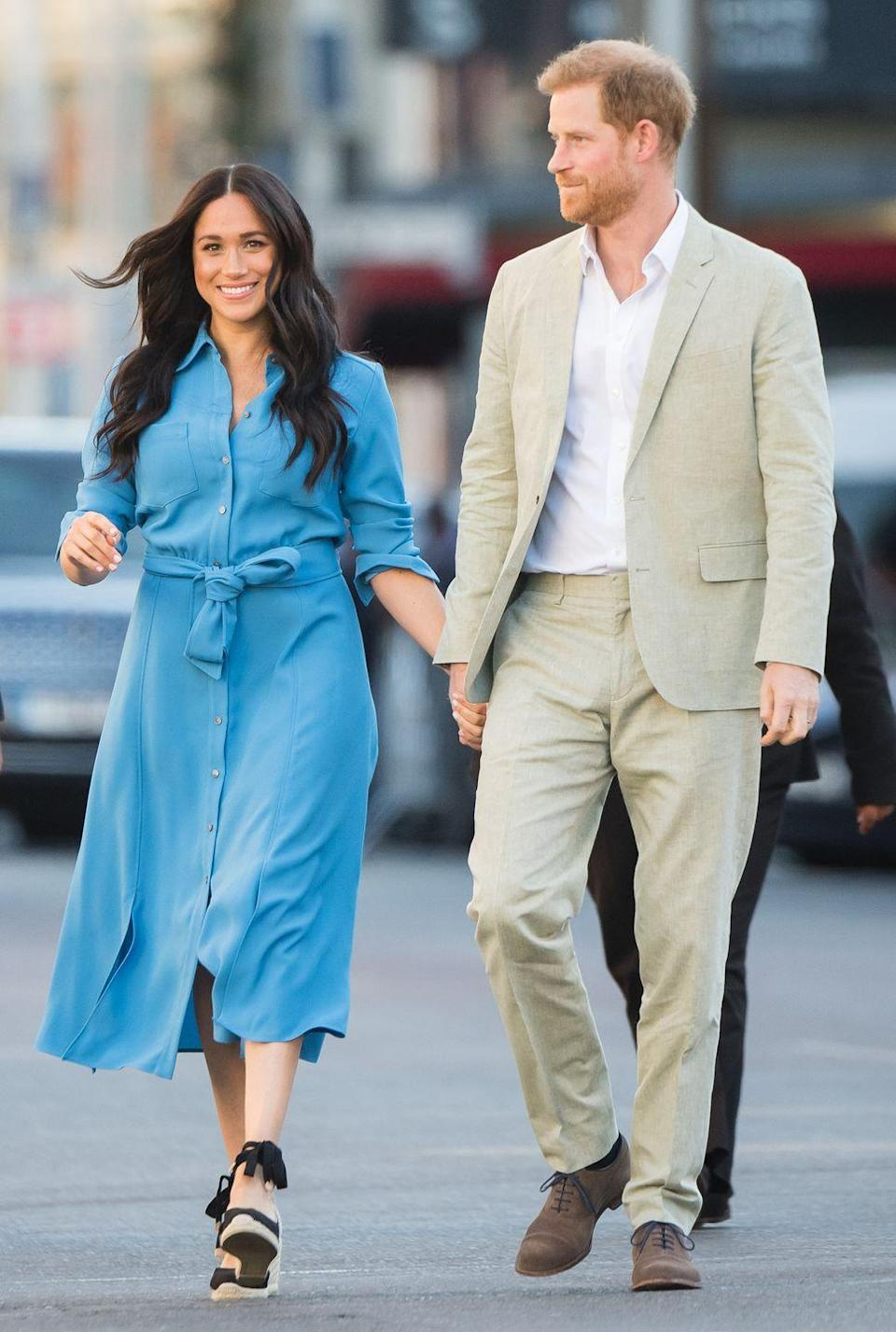 """<p>For her second engagement of the day, Meghan changed<a href=""""https://www.townandcountrymag.com/style/fashion-trends/a29190740/meghan-markle-blue-veronica-beard-dress-cape-town-photos/"""" rel=""""nofollow noopener"""" target=""""_blank"""" data-ylk=""""slk:into a gorgeous blue Veronica Beard dress"""" class=""""link rapid-noclick-resp""""> into a gorgeous blue Veronica Beard dress</a>, which the Duchess previously wore in Tonga last year. Meghan paired the striking outfit with the same black espadrilles she wore earlier in the day.</p>"""
