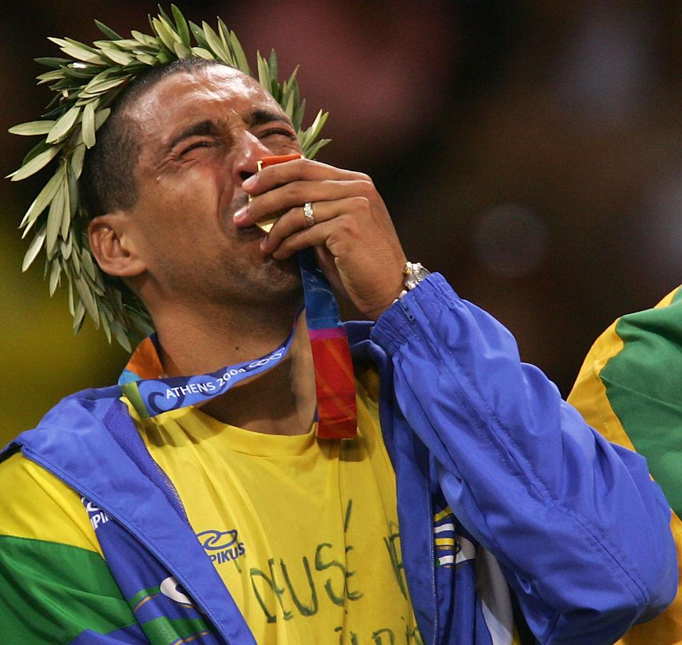 ATHENS - AUGUST 29: Sergio Dutra Santos #10 of Brazil cries as he kisses the gold medal for men's indoor Volleyball during ceremonies on August 29, 2004 during the Athens 2004 Summer Olympic Games at the Peace and Friendship Stadium part of the Faliro Coastal Zone Olympic Complex in Athens, Greece. Brazil defeated Italy to win gold. (Photo by Adam Pretty/Getty Images)