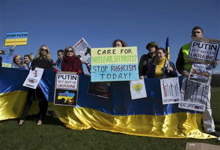 People hold posters and banners at an international protest during the Nuclear Security Summit at Malieveld in The Hague March 24, 2014. REUTERS/Cris Toala Olivares