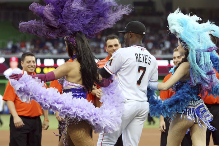Miami Marlins shortstop Jose Reyes (7) is escorted onto the field by women in carnival costumes for an Opening Day baseball game against the St. Louis Cardinals, Wednesday, April 4, 2012, in Miami. (AP Photo/Lynne Sladky)