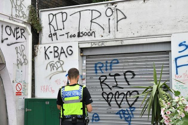 Flowers and three spray cans lay next to shutters, which have been spray-painted with
