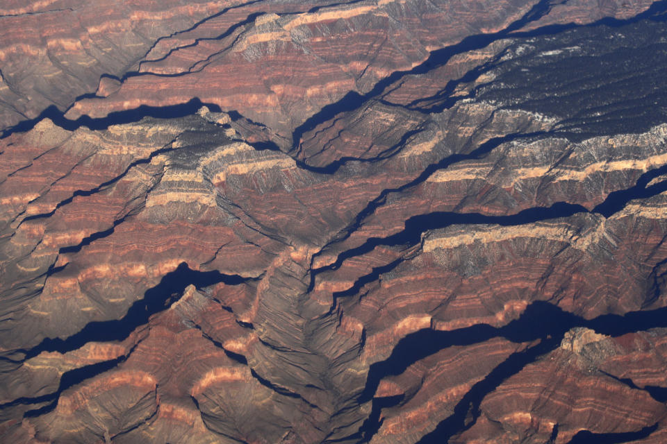 FILE - This Dec. 17, 2019 file aerial photo shows Arizona's Grand Canyon. A leading conservation agency is warning that climate change is damaging the U.N.' most cherished heritage sites. Climate change is increasingly damaging the U.N.'s most cherished heritage sites, a leading conservation agency warned Wednesday Dec. 2, 2020, reporting that Australia's Great Barrier Reef and dozens of other natural wonders are facing severe threats. (AP Photo/Charlie Riedel, File)