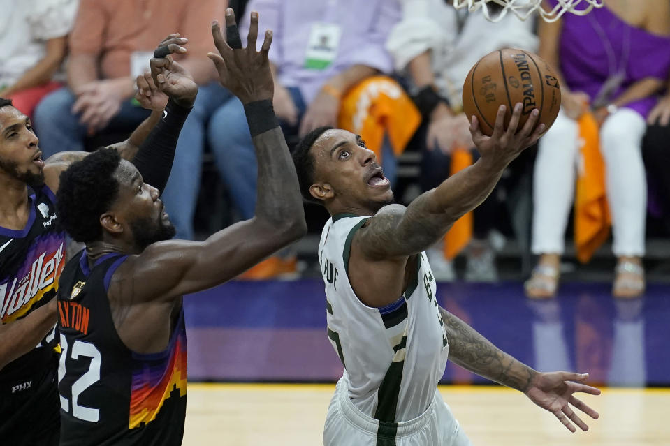 Milwaukee Bucks guard Jeff Teague, right, shoots against Phoenix Suns center Deandre Ayton during the first half of Game 5 of basketball's NBA Finals, Saturday, July 17, 2021, in Phoenix. (AP Photo/Ross D. Franklin)
