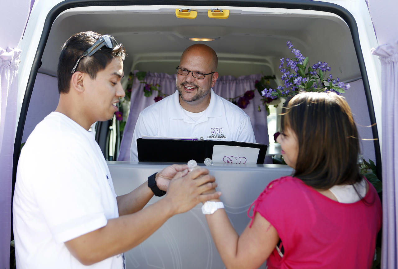 LAS VEGAS - OCTOBER 6:  The Rev. Andy Gonzalez (C) officiates a wedding vows renewal ceremony between Jay Junio (L) and Anne Junio of California at the Las Vegas Wedding Wagon in the parking lot of the Welcome to Fabulous Las Vegas sign on October 6, 2012 in Las Vegas, Nevada. For USD 99, ordained ministers will drive a van with an altar to any location in and around Las Vegas and perform a legal wedding, vow renewal or commitment ceremony in about 10 minutes. The fee includes wedding photos but not a marriage license. Couples can either get hitched at the Wedding Wagon's walk-up window or at iconic areas including the Welcome to Fabulous Las Vegas sign, the fountains at the Bellagio, the Hoover Dam and pedestrian bridges overlooking the Las Vegas Strip.  (Photo by Isaac Brekken/Getty Images)
