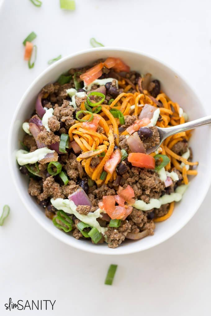 """<div><span>Per bowl (recipe yields 4)</span>: 411 calories, 13 g fat (5 g saturated), 316 mg sodium, 45 g carbs, 10 g fiber, 8 g sugar, 32 g protein</div> Sweet potato noodles and black beans team up to fuel your body with slow-digesting carbohydrates, knocking out a third of your daily quota of flat-belly fiber. Insufficient fiber intake can cause fatigue, prevent weight loss, and even increase the risk for heart disease. To make sure you're getting enough, women should aim for 25 grams a day, while men should consume closer to 38 grams. <strong>Get the recipe from <a rel=""""nofollow noopener"""" href=""""http://slimsanity.com/sweet-potato-noodle-taco-bowls"""" target=""""_blank"""" data-ylk=""""slk:Slim Sanity"""" class=""""link rapid-noclick-resp"""">Slim Sanity</a>.</strong>"""