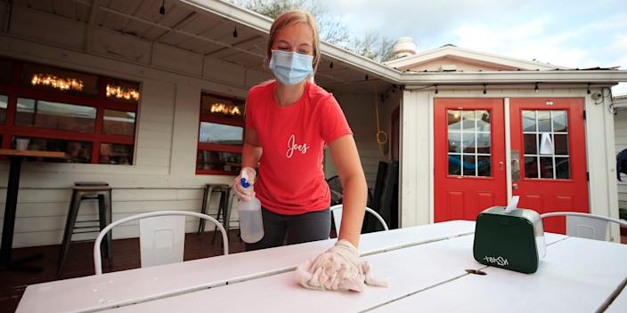 A worker at a restaurant in Louisville, Kentucky, cleans a table at a restaurant after it was allowed to reopen in May.