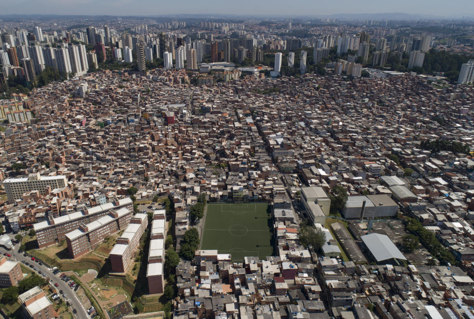 """FILE - In this April 6, 2020 file photo, the slum Paraisopolis, which is the combination of the words """"Paradise"""" and """"Metropolis,"""" stands next to the upper class Morumbi neighborhood, top, in Sao Paulo, Brazil. Packages started reaching doorsteps in this favela in April 2021 through a logistics startup that handles what retailers call """"the last mile,"""" communities that the global e-commerce revolution didn't fully include. (AP Photo/Andre Penner, File)"""