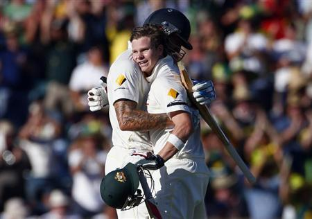 Australia's Steve Smith (R) hugs team mate Mitchell Johnson after reaching his century during the first day of the third Ashes cricket test against England at the WACA ground in Perth December 13, 2013.