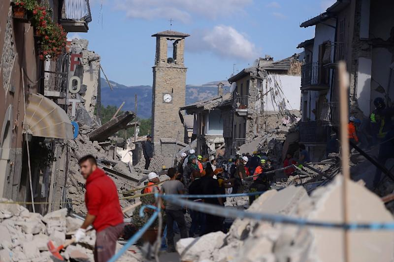 Rescuers and firemen search the rubble of buildings in Amatrice, central Italy on August 24, 2016 following the earthquake that struck before dawn
