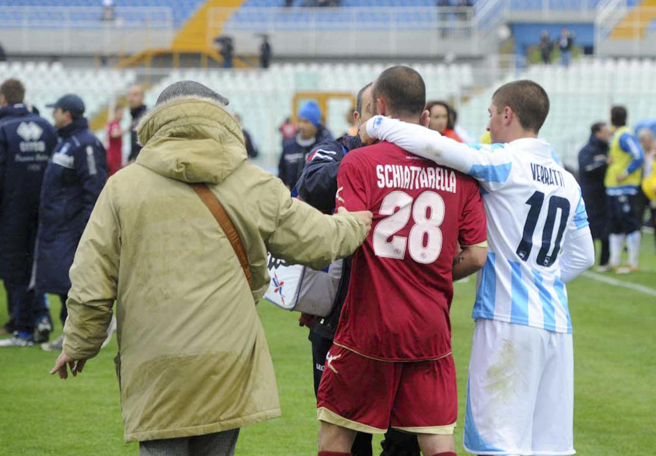 Livorno's Pasquale Schiattarella, center, and Pescara's Marco Verratti, right, confort each other as medics assists Livorno's Piermario Morosini, not shown, at the Pescara's Adriatico stadium, central Italy, Saturday, April 14, 2012, during a Serie B soccer match between Pescara and Livorno. Morosini, who was on loan from Udinese, fell to the ground in the 31st minute of the match and received urgent medical attention on the pitch. A defibrillator was also used on the 25-year-old. The match was called off, with the other players leaving the field in tears. (AP Photo/Cristiano Chiodi, Lapresse) ITALY OUT