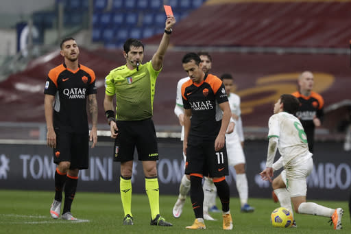 Roma's Pedro, centre, is shown the red card by the referee after a foul on Sassuolo's Maxime Lopez, right, during a Serie A soccer match between Roma and Sassuolo at the Olympic Stadiumin Rome, Italy, Sunday, Dec. 6, 2020. (AP Photo/Andrew Medichini)