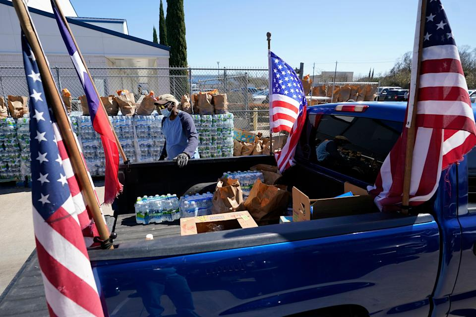 Food and water are loaded into the back of a pickup truck at a distribution site on Feb. 22, 2021, in Houston. The city's boil-water notice has been rescinded however many residents lack water at home due to broken pipes.