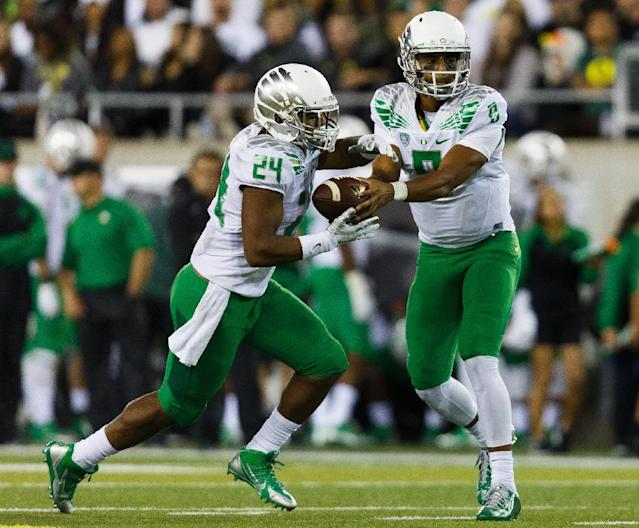 Oregon quarterback Marcus Mariota (8) hands off to running back Thomas Tyner (24) during the second quarter of an NCAA college football game against South Dakota in Eugene, Ore., Saturday, Aug. 30, 2014. (AP Photo/Ryan Kang)