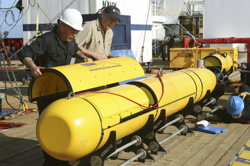 In this Monday, April 14, 2014, photo provided by the Australian Defense Force Phoenix International's Chris Minor, left, and Curt Newport inspect an autonomous underwater vehicle before it is deployed from ADV Ocean Shield in the search of the missing Malaysia Airlines Flight 370 in the southern Indian Ocean. The search area for the missing Malaysian jet has proved too deep for the robotic submarine which was hauled back to the surface of the Indian Ocean less than half way through its first seabed hunt for wreckage and the all-important black boxes, authorities said on Tuesday. (AP Photo/Australian Defense Force, Lt. Kelli Lunt) EDITORIAL USE ONLY