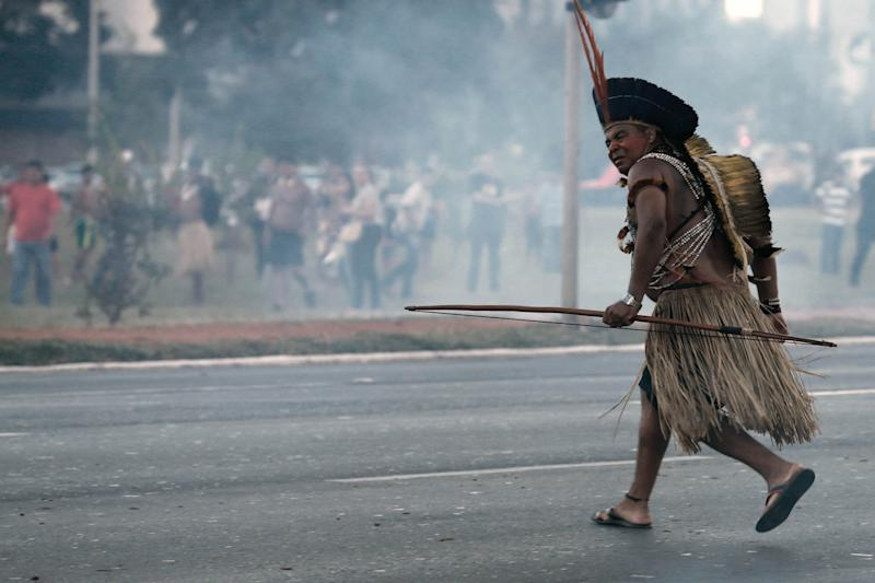 An Indigenous protester in traditional headdress runs with his bow