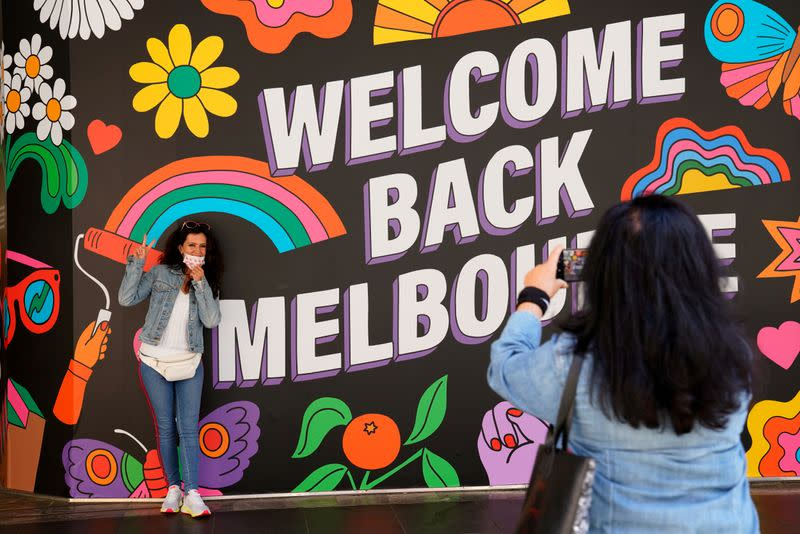 FILE PHOTO: People take photos in front of a 'Welcome Back' sign after coronavirus disease restrictions were eased in Melbourne