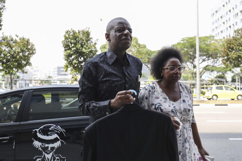 Adam Molai, left, and a relative arrive at the Singapore Casket funeral parlor building where the body of the late former president of Zimbabwe is being held on Saturday, Sept. 7, 2019, in Singapore. Robert Mugabe, the former leader of Zimbabwe forced to resign in 2017 after a 37-year rule whose early promise was eroded by economic turmoil, disputed elections and human rights violations, has died in Singapore. He was 95. (AP Photo/Danial Hakim)
