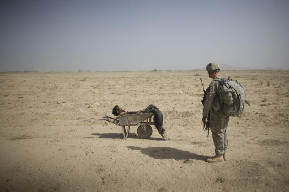A U.S. Army soldier from Scout Platoon 502 Infantry Regiment, 101st Airborne Division, looks at the body of a suspected Taliban IED emplacer who was killed in a coalition missile strike in Zhari district, Kandahar province, Sunday, Oct. 10, 2010. The Scouts' mission was to support roadside bomb clearance efforts in the militant stronghold, the latest days-long phase of Operation Dragon Strike. (AP Photo/Rodrigo Abd)