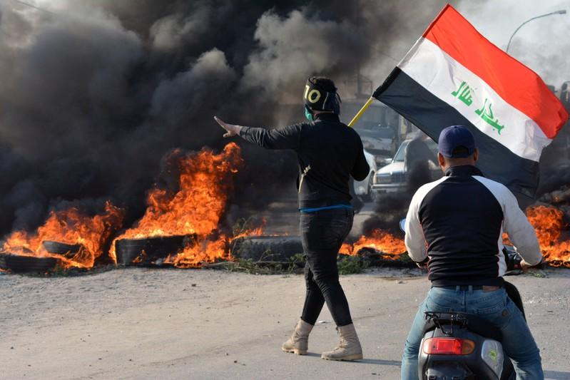 A demonstrator holds an Iraqi flag near  burning tires during ongoing anti-government protests in Nassiriya