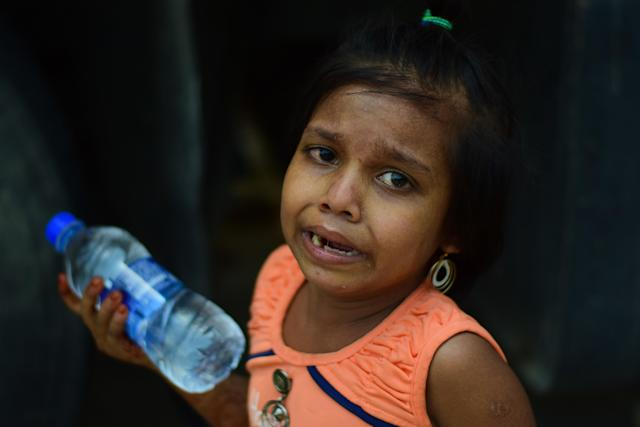MUMBAI, MAHARASHTRA, INDIA - 2020/05/13: A girl cries as they wait to board vehicles during the lockdown. Due to lockdown situation, most migrants are stuck in Mumbai, some walk and others arrange their own trucks and buses to their home towns, while the police say that the buses are available by the government. (Photo by Ratika More/SOPA Images/LightRocket via Getty Images)