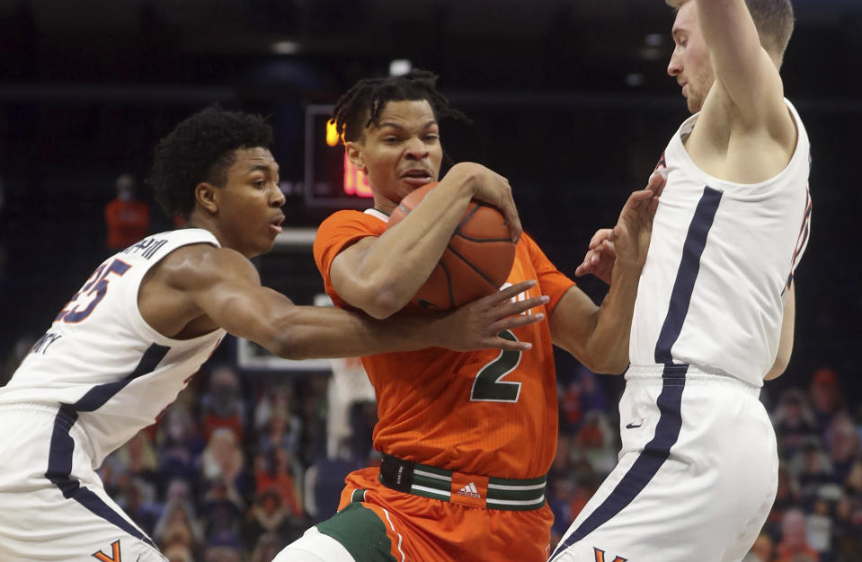 Miami guard Isaiah Wong (2) is pressured by Virginia guard Trey Murphy III (25) and forward Sam Hauser, right, during an NCAA college basketball game Monday in Charlottesville, Va. (Andrew Shurtleff/The Daily Progress via AP, Pool)