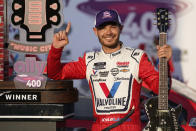 FILE - Kyle Larson celebrates with the winner's guitar and trophy after winning a NASCAR Cup Series auto race at Nashville Superspeedway in Lebanon, Tenn., in this Sunday, June 20, 2021, file photo. Rick Hendrick gave Kyle Larson a second chance in NASCAR because Hendrick Motorsports had wanted him in its lineup for years. Now that Hendrick has his man, he's locked Larson down for two more seasons with full sponsorship. Hendrick on Wednesday, July 14, told his 93 dealerships that the hottest driver in motorsports signed a contract extension through 2023 and Larson will be fully sponsored by HendrickCars.com. (AP Photo/Mark Humphrey, File)