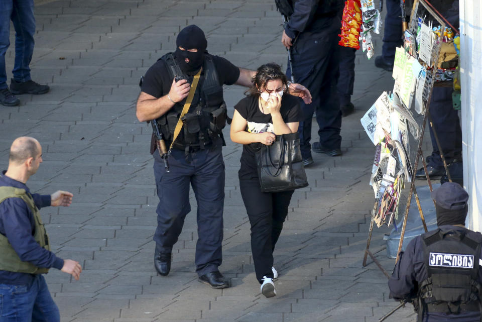 """Georgian police officers escorts a woman who escaped from a bank where an armed assailant has taken several people hostage, in the town of Zugdidi in western Georgia, Wednesday, Oct. 21, 2020. The Georgian Interior Ministry didn't immediately say how many people have been taken hostage in the town of Zugdidi in western Georgia, or what demands the assailant has made. Police sealed off the area and launched an operation """"to neutralize the assailant,"""" the ministry said in a statement. (AP Photo/Zurab Tsertsvadze)"""