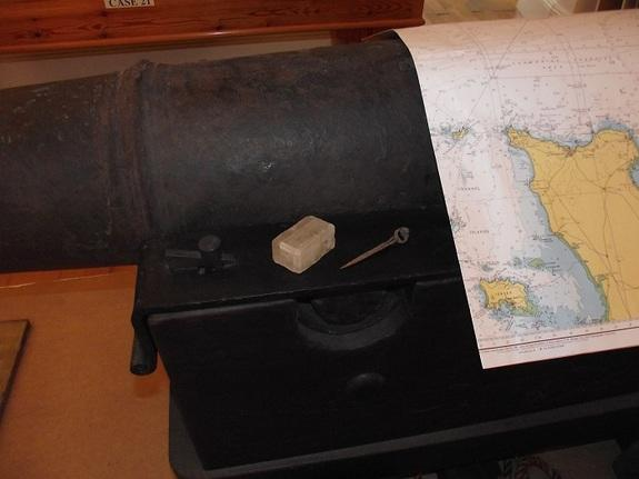 This image shows the original calcite crystal alongside Elizabethan navigation dividers on top of a cannon. All of these artifacts were raised from the site of the Alderney wreck.