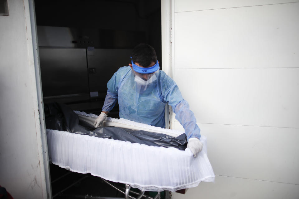 FILE - In this April 23, 2021 file photo, a healthcare worker pushes a coffin that contains the remains of a patient who died from COVID-19, at the Dr. Norberto Raul Piacentini hospital, in Lomas de Zamora, Argentina, amid the new coronavirus pandemic. The South American country recorded on Wednesday, July 14, 2021, more than 100,000 deaths from COVID-19 since the pandemic began. (AP Photo/Natacha Pisarenko, File)