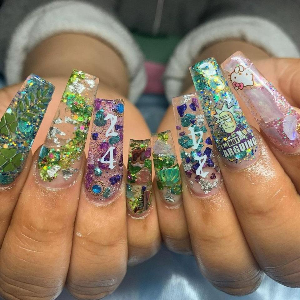 """London-based nail artist <a href=""""https://www.instagram.com/imoannails/"""" rel=""""nofollow noopener"""" target=""""_blank"""" data-ylk=""""slk:Naysap"""" class=""""link rapid-noclick-resp"""">Naysap</a> put together this encapsulated freestyle set. Her client picked out a few stickers and glitter acrylic and let the artist go to work. There's an interesting mix of decals like the green four-leaf clovers, the Rick Sanchez sticker, and the tiny Hello Kitty. The random assortment of stickers works with the various green, blue, and purple shades of glitter to tie this manicure together."""