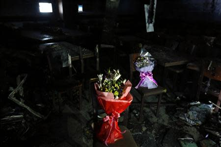 Bouquets are placed on burnt chair at a dining room of a migrant shelter destroyed by an arson attack in Seoul October 14, 2013. REUTERS/Kim Hong-Ji
