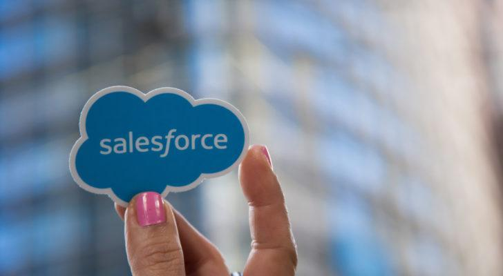 A hand with pink painted fingernails holds a Salesforce (CRM) sticker.