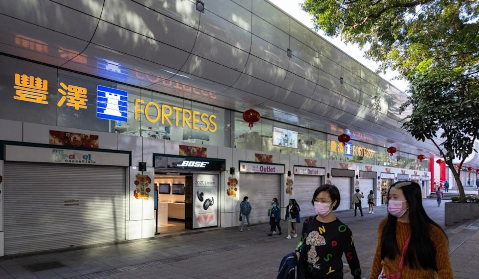 Pedestrians walk past a row of mostly closed stores on a popular shopping strip in Tsim Sha Tsui on Sunday. Photo: Bloomberg