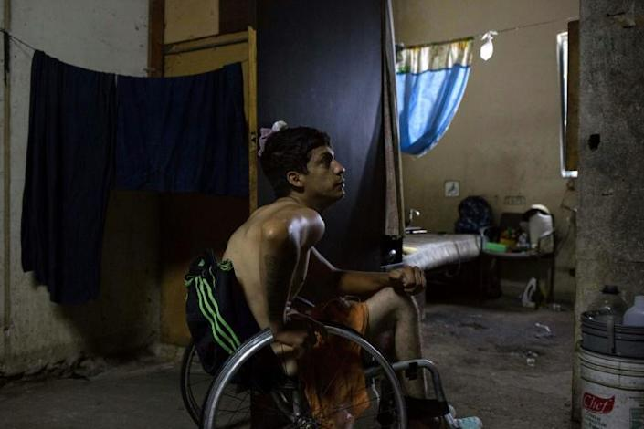 Johan Medina sits in his wheelchair by his room at a shelter located in the basement of the Sudameris public building in Caracas