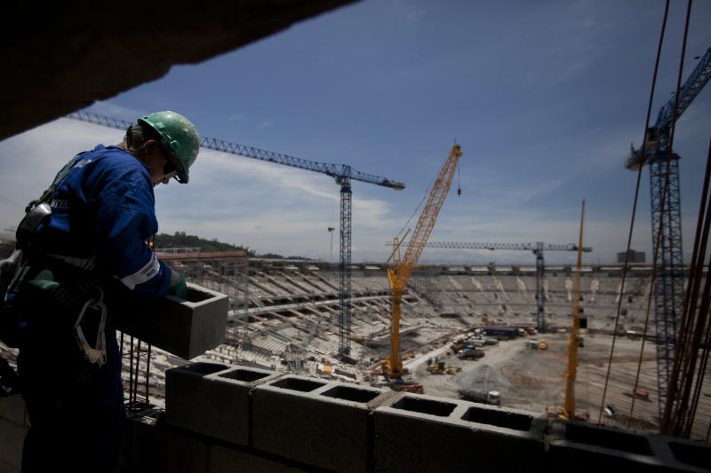 A construction worker lays blocks at the Maracana soccer stadium as it undergoes renovations during a tour for journalists organized by the Rio 2016 Committee in Rio de Janeiro, Brazil, Monday, Nov. 19, 2012. The IOC Official Debriefing of the London 2012 Games will take place from Nov. 17 to 21 in Rio de Janeiro.  (AP Photo/Felipe Dana)
