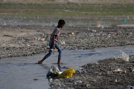 A boy crosses a drain on the banks of the river Ganges in Kanpur
