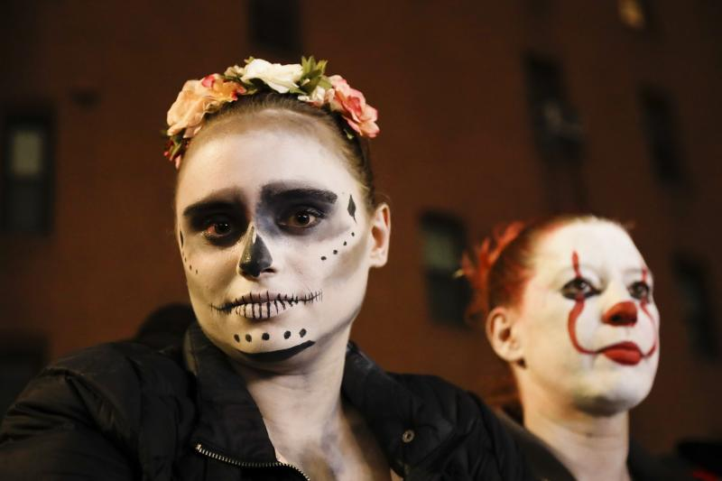 Leni Wild poses with others as they watch revelers march during the Greenwich Village Halloween Parade, Thursday, Oct. 31, 2019, in New York. (AP Photo/Frank Franklin II)