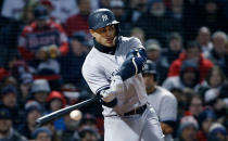 New York Yankees' Giancarlo Stanton hits a single during the fifth inning of the team's baseball game against the Boston Red Sox in Boston, Tuesday, April 10, 2018. (AP Photo/Michael Dwyer)