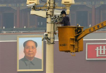 A man works on a security camera that was installed at Tiananmen Square in Beijing