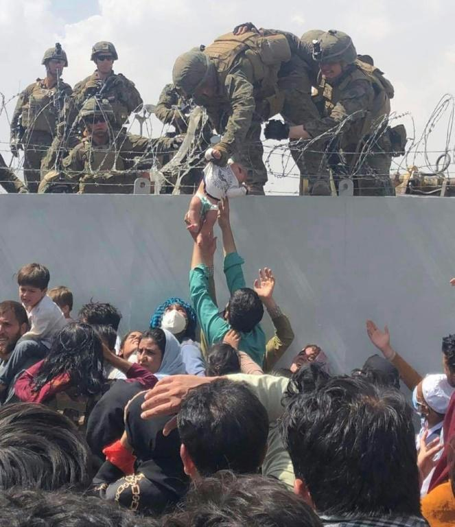 Footage of an Afghan child being handed off to a US Marine over a wire-topped wall at Kabul's airport went viral on social media