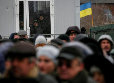 FILE PHOTO: People line up after crossing the contact line between pro-Moscow rebels and Ukrainian troops as they wait at passport control in Mayorsk